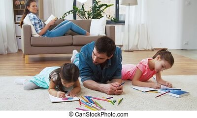 father with little daughters drawing at home