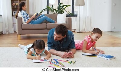 father with little daughters drawing at home - family,...