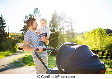 Father with little son and baby daughter in stroller. Sunny...