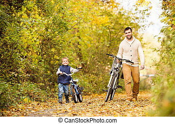 Father with little son cycling in autumn park. - Young...