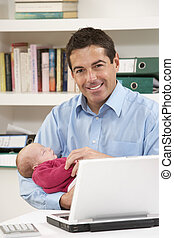 Father With Newborn Baby Working From Home Using Laptop