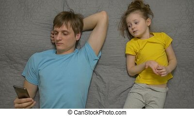 Father with phone ignore daughter daytime looking at smartphone addiction male 30 years old in blue t shirt caucasian white european lying on the bed disregard child little girl female caucasian white european 5 years old in yellow t shirt on gray sheet top view.