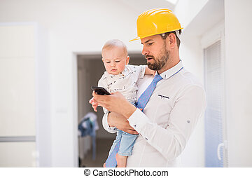 Father with shirt, tie, helmet and smartphone holding a baby son at home.