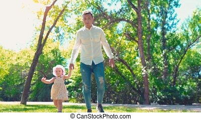 Father with small daughter running in summer park holding hands directly on camera, girl looking at camera