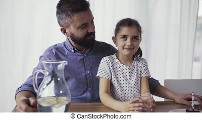 Father with small daughter sitting at the table indoors at...