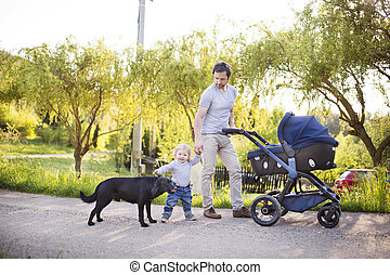 Father with son and baby daughter in stroller. Sunny park.