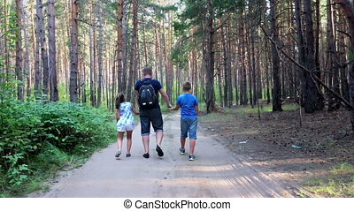 Father with son and daughter walking in forest