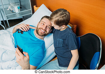 father with son embracing while laying on hospital bed at ward, hospital patient care