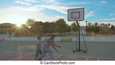 Father with son enjoy a day at the park and playing basketball.