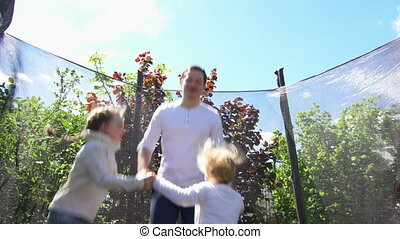 Father with son have fun on trampoline. Slow motion shot.