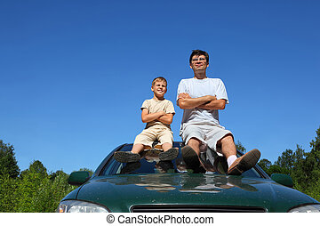Father with  son of sit on   roof of car in   day and peep in  distance, laying down hands on  breast
