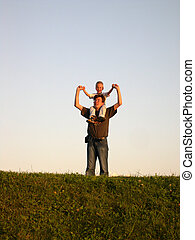 father with son on shoulders on sundown
