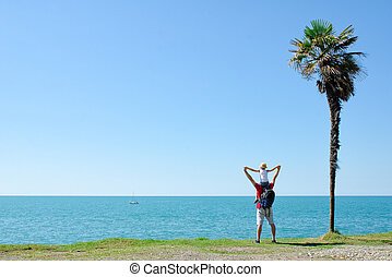 Father with son on shoulders stands back against the backdrop of tall palm, sea and blue sky