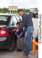 Father with son refueling car on gas station together
