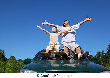 Father with son sit on roof of car, lift person in sky and ...