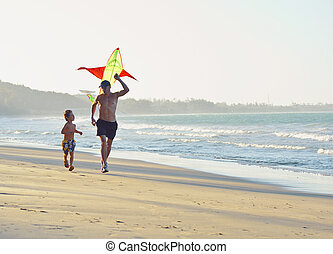 father with son, sunset at the seacoast playing kite, happy family