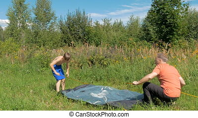 Father with son together are setting a tourist tent