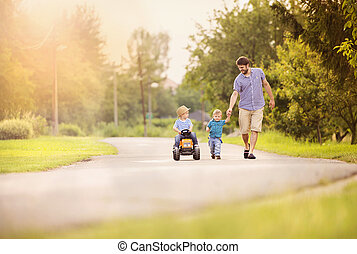 Father with sons have fun on road - Happy young father with...