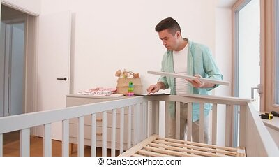 father with tablet pc assembling baby bed at home -...