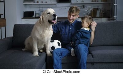 Father with toddler son and dog sitting on sofa