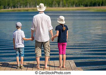 father with two children admire the beautiful scenic lake, view from the back