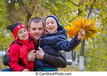 Father with two children in autumn park