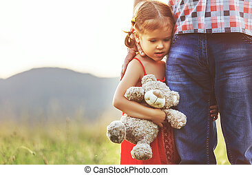 Father's day. Child girl hugging father in nature at sunset