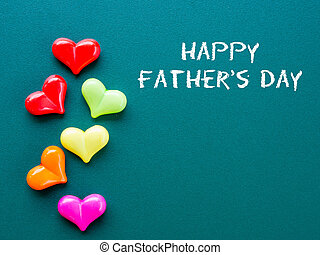 Father's day concept. HAPPY FATHER'S DAY text with colorful heart and gift on green background
