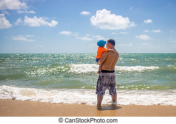 father's day. dad and baby in his arms look at the sea waves standing on sandy beach