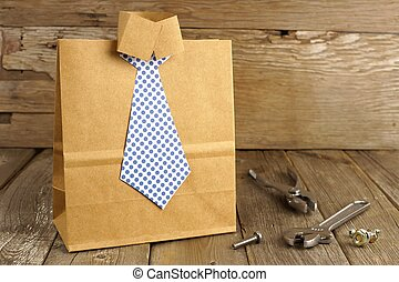 Fathers Day handmade shirt and tie gift bag with tools on a wood background