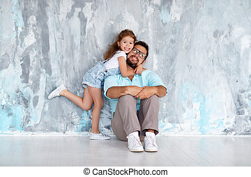 Father's day. Happy family daughter hugging dad and laughs near an wall