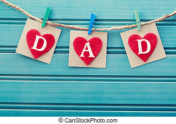 Fathers day message on felt hearts over blue wooden board