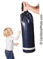 father's hands is holding punching bag and little girl is punching it. isolated.