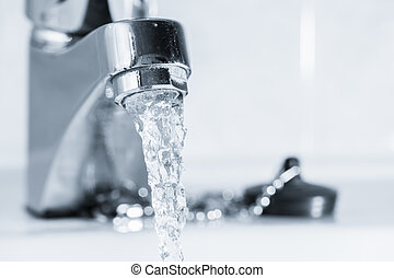 Open faucet in bathroom, water is running, tinted black and white image, horizon format