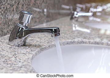 faucet with water flow on sink in luxury bathroom