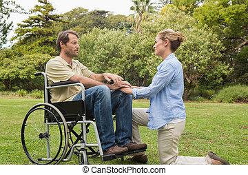fauteuil roulant, contenu, associé, agenouillement homme, à côté de, lui