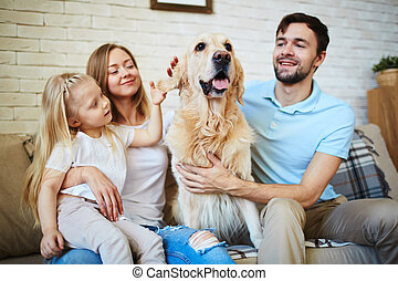 Modern family with pet resting on sofa at home