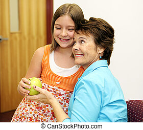 A cute school girl giving an apple to her favorite teacher.
