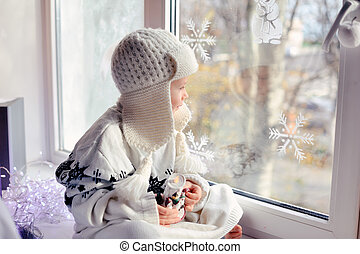 favorite window - winter boy sitting by the window in a...