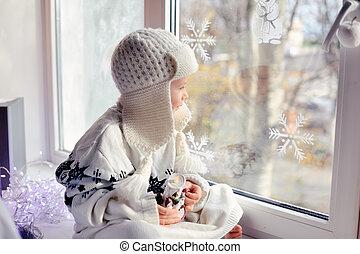 favorite window - winter boy sitting by the window in a...