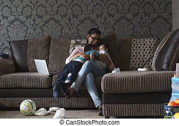 Young mother enjoying a cuddle with her two sons. She has the baby in her arms, who's brother is snuggling in to him.