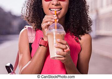 Joyful happy woman holding an orange straw