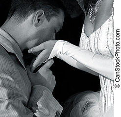 The groom kisses the bride in hands. b/w