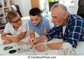 Pleasant aged man sitting together with his grandchildren