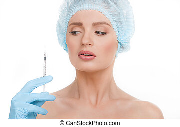 Fear of injections. Portrait of terrified young woman in medical headwear looking at the hand holding syringe near her face isolated on white