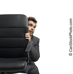 Fear - Concept of fear of a businessman behind a chair