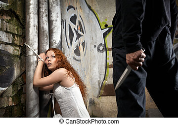 Fear - Tied woman is looking at a man with a knife