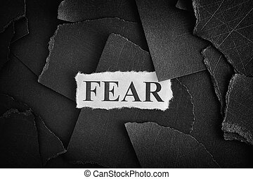 Fear. Torn pieces of black paper and word Fear