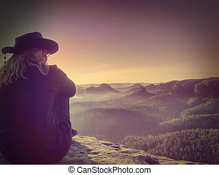 Fearless blond middle age hiker woman on the Edge