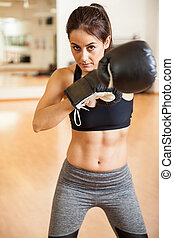 Fearless female boxer with toned abs